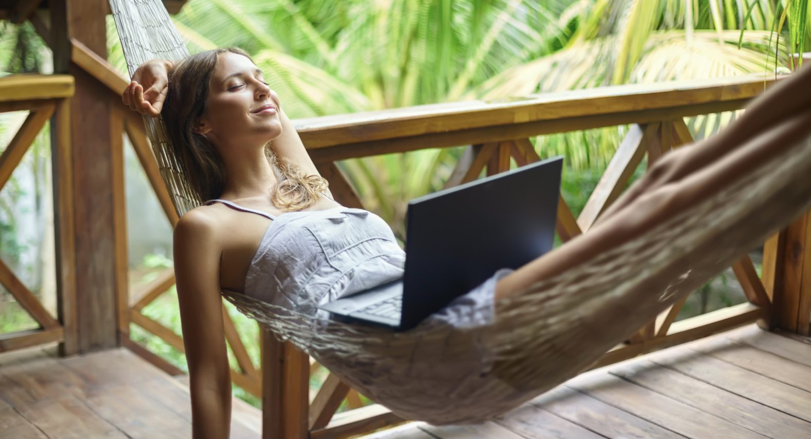 Young beautiful woman relaxing in a hammock with laptop in a tropical resort. Break time